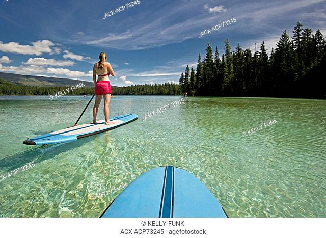 A pair of paddle boarders make their way across the tropical like waters of Johnson Lake, North of Kamloops in the Thompson Okanagan region of British Columbia