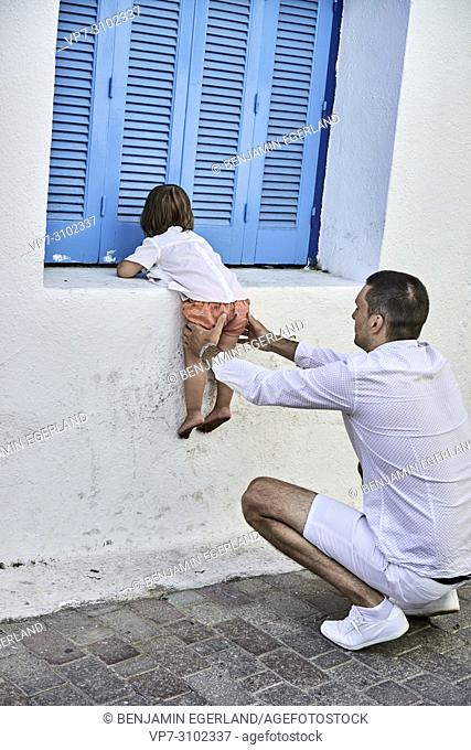 father helping toddler daughter to climb on windowsill, learning, caring, fatherhood, responsibility