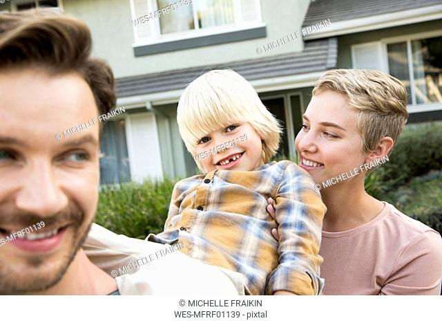 Portrait of happy parents with son in front of their home