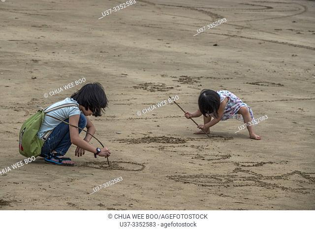 Children draw pictures on the beach, Telok Melano , Sematan, Sarawak, Malaysia