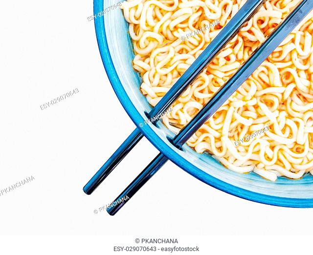 Above view of spicy instant noodles inblue bowl with chopsticks isolated on white background