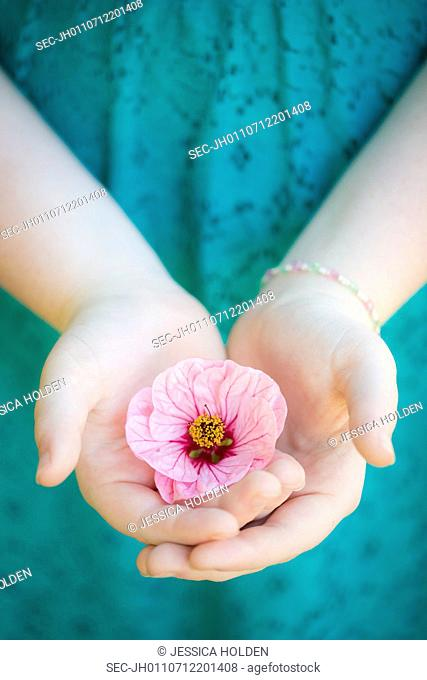 Teenage girl (13-15) with flower in hand