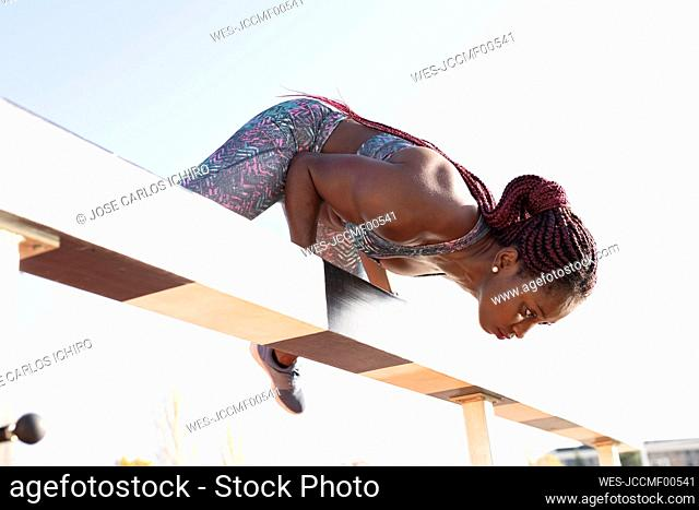 Female athlete with braided hair balancing on beam against clear sky during sunny day