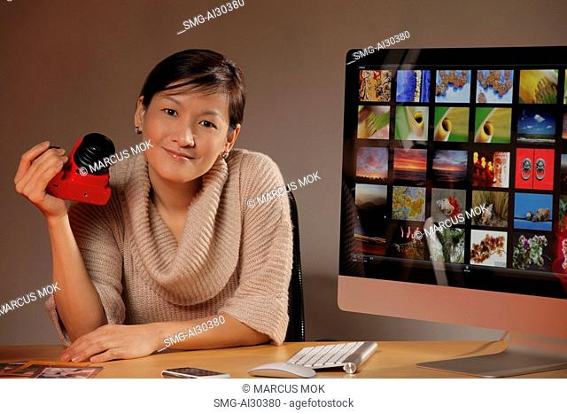 Woman holding a camera and sitting next to a computer of photos