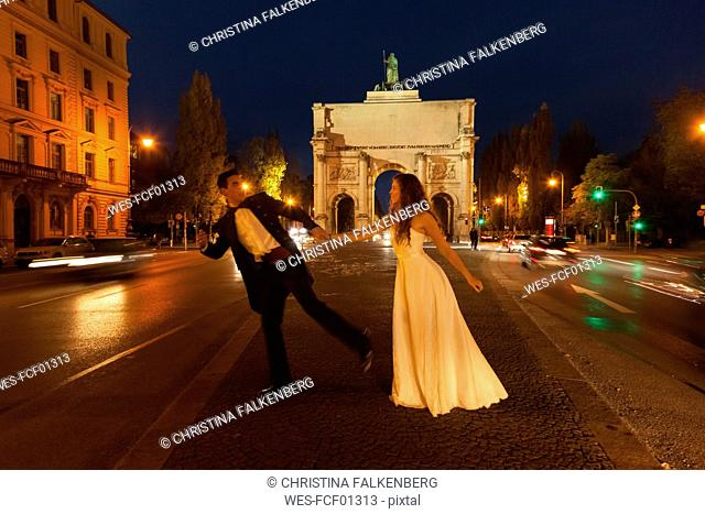 Happy bridal couple crossing Leopold Street in Munich at night