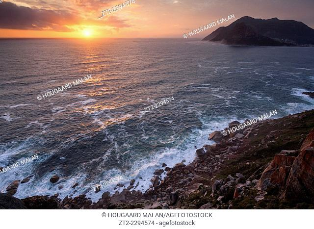 Wide angle photo of a dramatic sunset beyond the cliffs of Chapmans Peak pass and Houtbay. Chapmans Peak, Cape Town, South Africa