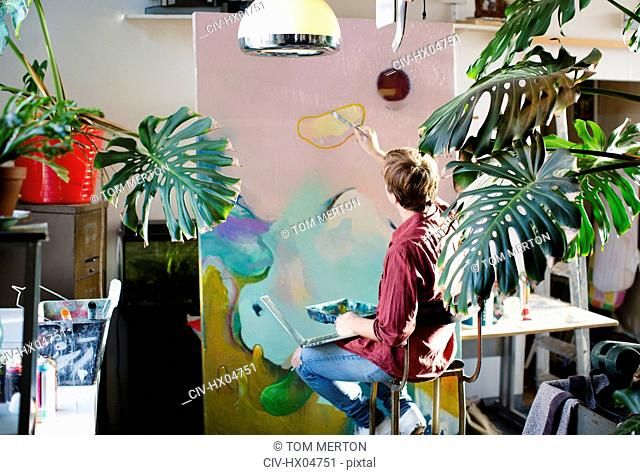 Male artist painting on large canvas in apartment