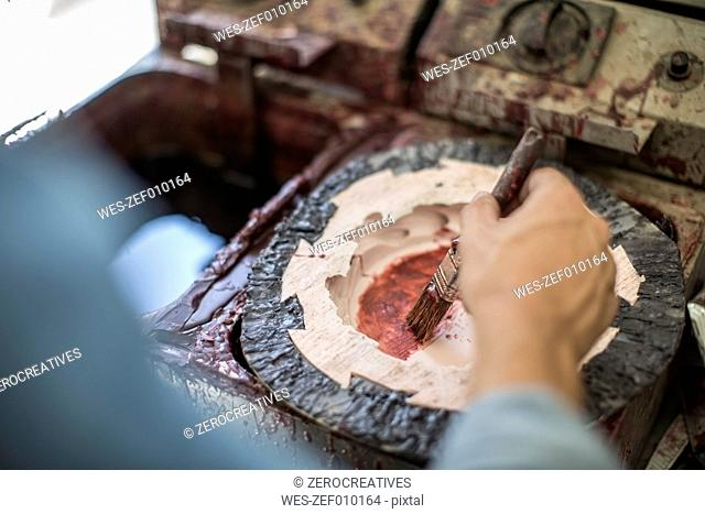 Artist painting wax in mould