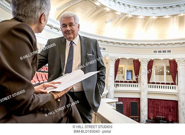 Caucasian politicians talking in capitol building