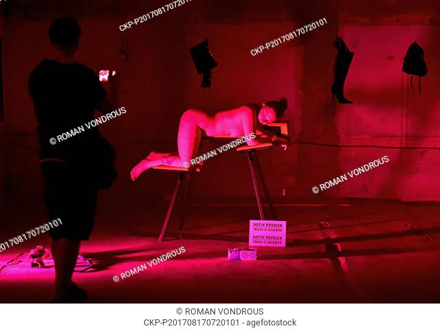 One of 13 naked woman exhibits herself during the three-day exhibition named Voayer, which shows 13 naked women mostly in submissive positions, in Prague