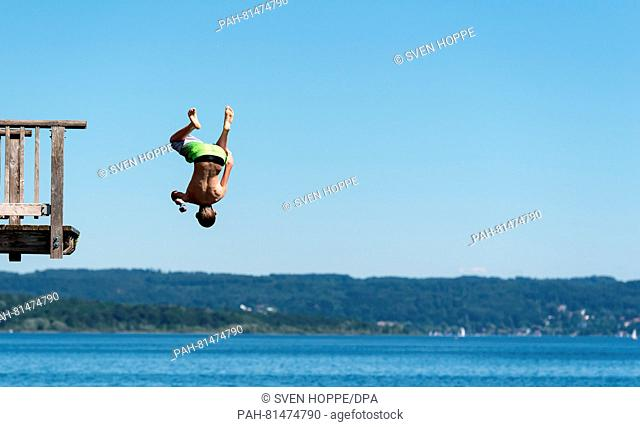 A youth jumping into Ammersee lake from a wooden diving tower at the bathing beach at Utting, Germany, 23 June 2016. PHOTO: SVEN HOPPE/DPA | usage worldwide
