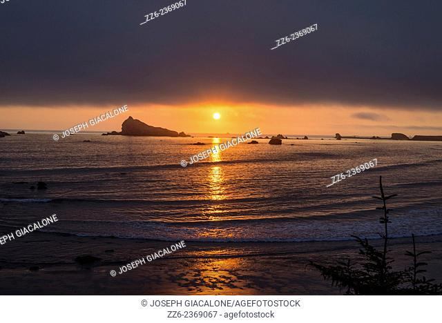The setting Sun reflecting off of the ocean. Viewed from above Pebble Beach. Crescent City, CA, USA