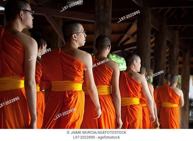 Saffron robbed monks leave morning prayers near the Wat Pak Nam temple, Bangkok Thailand