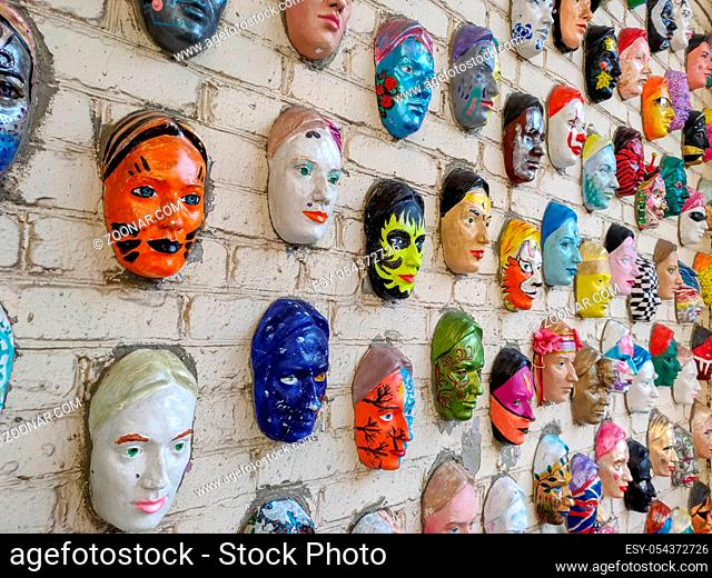 Moscow, Russia, 21 October 2019: Colorful painted ceramic faces sculpture on the bricks wall as an the object of modern art
