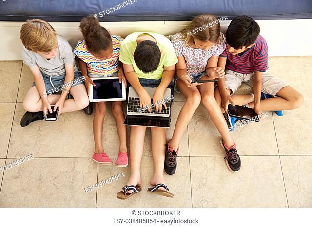 Overhead Shot Of Children Sitting On Floor Using Technology
