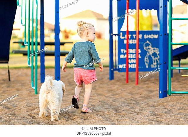 A young girl and her pet dog playing in a playground on a warm fall day; Spruce Grove, Alberta, Canada