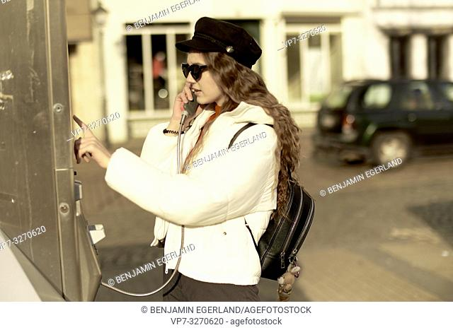 young woman dialling number at payphone, calling, in city Cottbus, Brandenburg, Germany