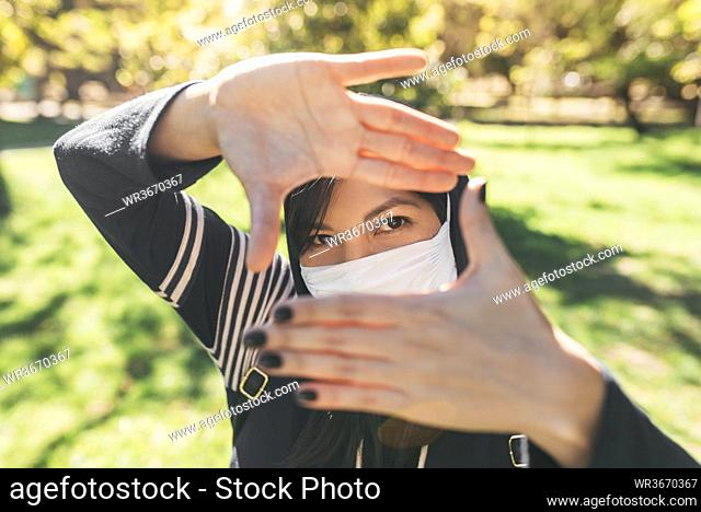 Close-up of young woman wearing mask looking through finger frames in park