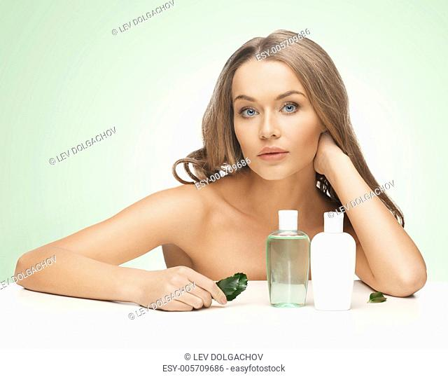 picture of woman with cosmetic bottles and leaf