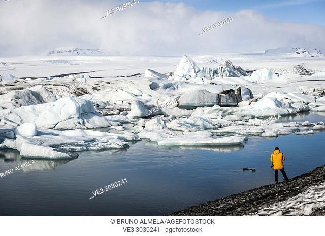 Photographer in Jökulsárlón Glacier Lagoon, Breidamerkurjökull Glacier (region of Austurland, Iceland)