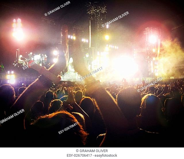 Large crowd at a concert. It is dark and there are colourful lights