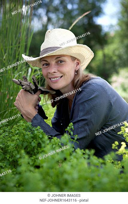 Portrait of smiling mature woman working in garden