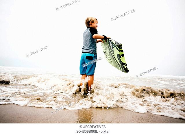 Young boy standing in sea, holding bodyboard