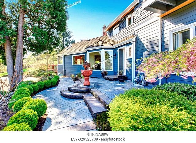Gorgeous back yard with patio including elegant fountain and lots of greenery