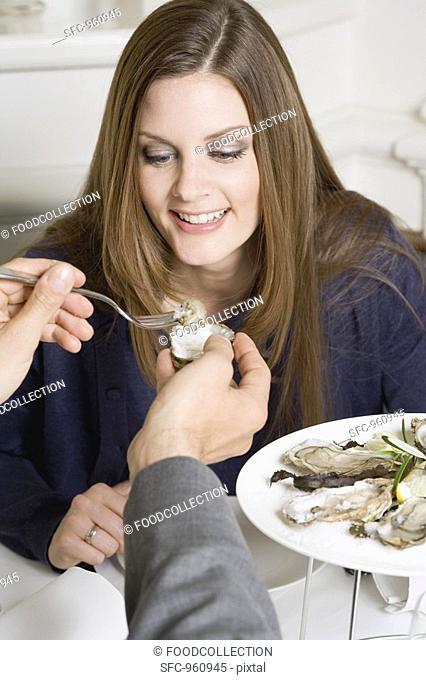 Man offering woman fresh oyster in restaurant