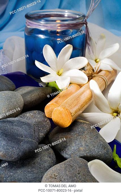 Spa elements, candle, flowers, Hawaiian hula sticks and grey stones