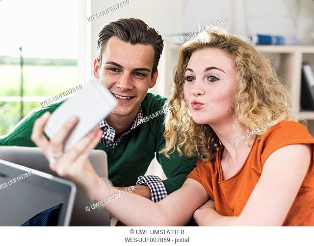 Two smiling young professionals looking at cell phone