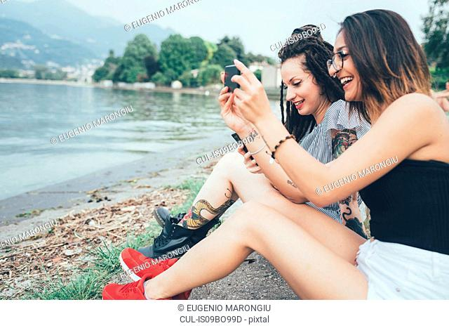 Girlfriends using mobile phone on beach