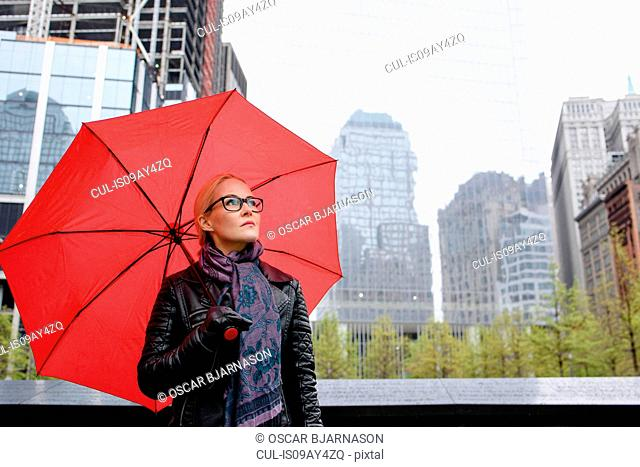 Female tourist with red umbrella looking up from One World Trade Center, New York, USA