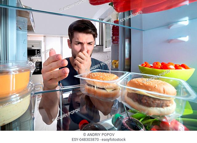 Young Man Holding His Nose After Recognizing Bad Smell Coming Out From The Refrigerator