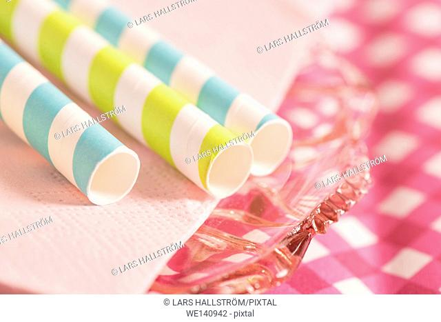 Striped straws and glass plates on table. Preparation for party or celebration. Concept of food styling or colorful birthday decoration