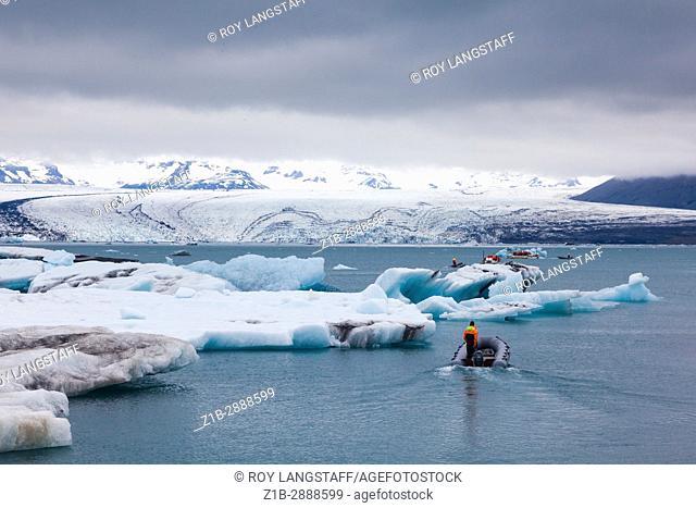 Tour boat operators and patrol boats amid icebergs on the Jokulsarlon glacial lagoon