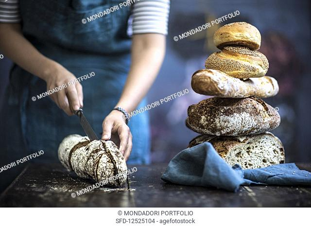 A woman halving a loaf of bread next to a stack of bread on a wooden table