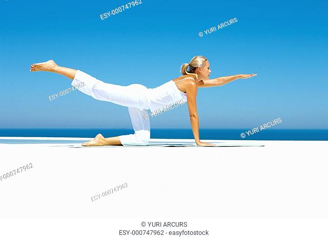 Mature sexy woman practicing yoga by the beach