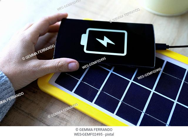 Renewable energy technology, solar panel charging a mobile phone battery