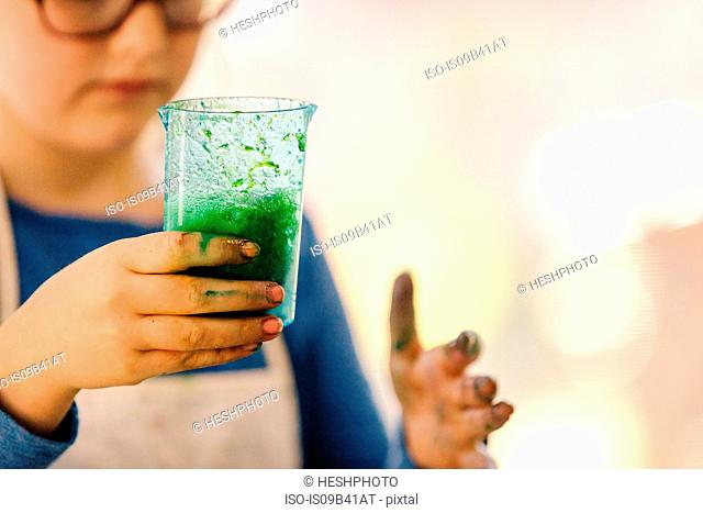 Girl doing science experiment, holding flask of green liquid