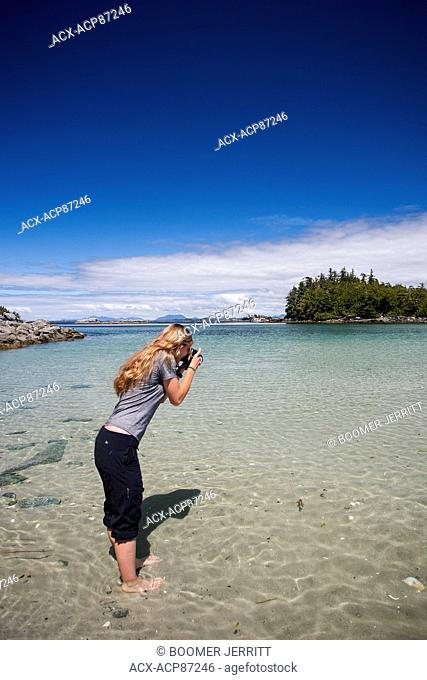 A young female photographer photographs a west coast scenic while exploring at the Mcmullin group of Islets. The great bear rain forest,Fiordland