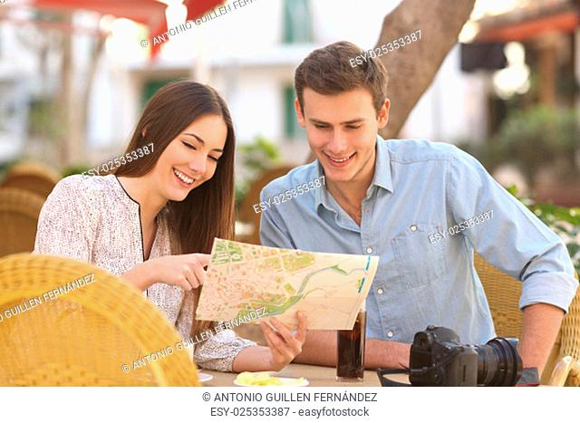 Happy couple tourists consulting a guide in a restaurant terrace