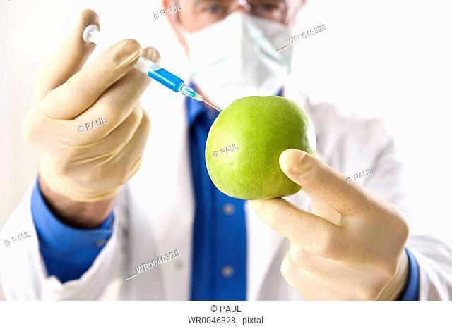 Scientist injecting granny smith apple