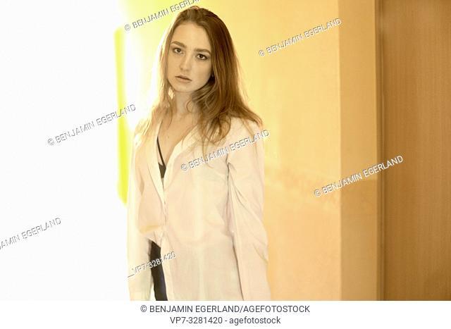 young reproachful woman indoors, orange, in Cottbus, Brandenburg, Germany