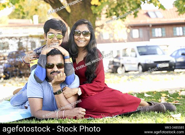 Indian family relaxing on the grass. Tegernsee, Bavaria, Germany