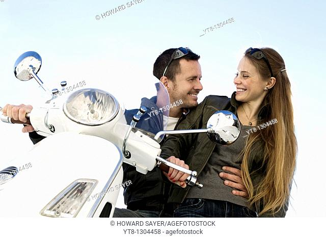 Couple sitting on a motor scooter and embracing
