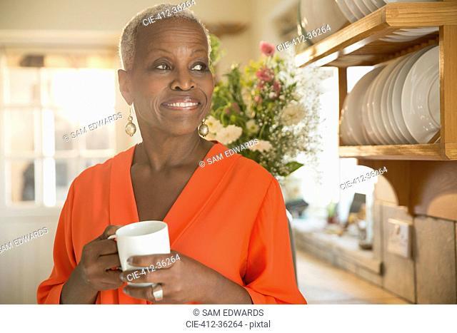 Smiling senior woman drinking coffee in kitchen
