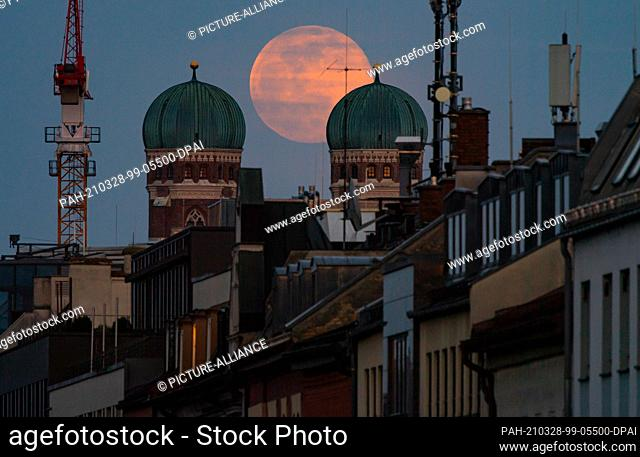 28 March 2021, Bavaria, Munich: The full moon stands between the twin towers of the Frauenkirche, which is located in the center of the Bavarian capital