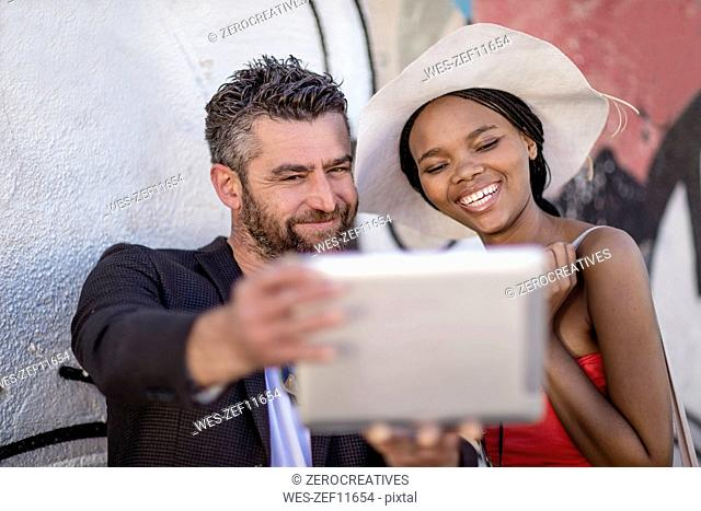 Smiling man and woman taking a selfie with tablet