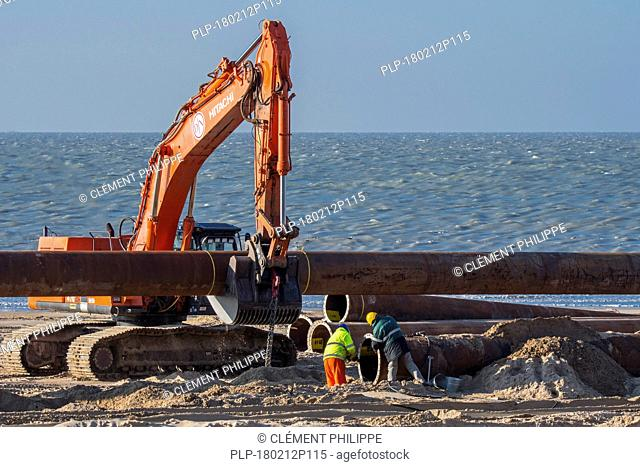 Dredging workers connecting pipes of pipeline during sand replenishment / beach nourishment works along the Belgian coast at Ostend, Belgium